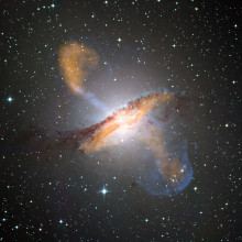 This composite of visible, microwave (orange) and X-ray (blue) data reveals the jets and radio-emitting lobes emanating from Centaurus A's central black hole.