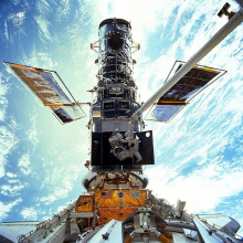 Astronauts Steven L. Smith, and John M. Grunsfeld, appear as small figures in this wide scene photographed during extravehicular activity (EVA). On this space walk they are replacing gyroscopes, contained in rate sensor units (RSU), inside the Hubble...