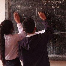 Schoolchildren writing on a blackboard