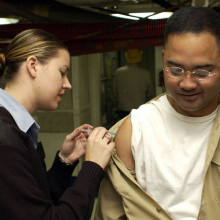 Hospital Corpsman 3rd Class Tiffany Long administers the influenza vaccination to a crew member aboard USS Kitty Hawk