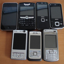 Assorted smartphones. From left to right, top row: iPhone 3G, Blackberry 8820, Nokia N78, Nokia N81, (bottom row) Nokia N95, Nokia E65, Nokia N70.