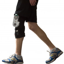 The biomechanical energy harvester comprises an aluminium chassis and generator (cylindrical component at the top of the chassis with green plastic attached) mounted on a customized orthopaedic knee brace (black), totalling 1.6 kg mass.
