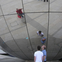 Spherical mirror in Millennium Square, Bristol, England. The photographer is seen top right in the blue shirt. The mirror forms the side of the Explore-At-Bristol Planetarium sphere.