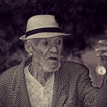 Elderly man holding a watch