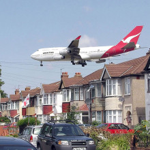 A Qantas Boeing 747-400 approaching runway 27L at London Heathrow Airport, England. The houses are in Myrtle Avenue, at the south east corner of the airport.