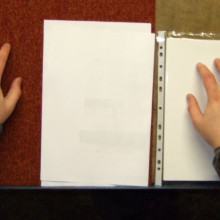 Rubbing the paper with both hands.