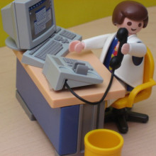 A Playmobil man sitting at a desk