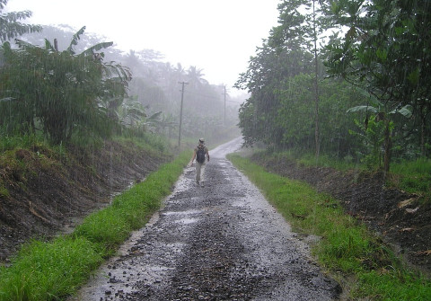 A person walking along a dirt track in the rain