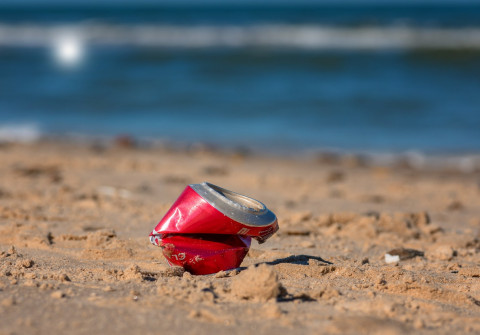 A crushed drinks can on a beach.